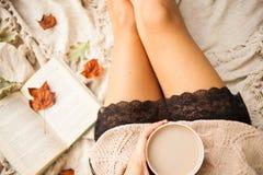 En flicka i en varm tröja sitter på en beige woolen filt och rymmer rånar av varmt kaffe i hennes händer Höstlivstail hem- comfor fotografering för bildbyråer