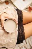 En flicka i en varm tröja sitter på en beige woolen filt och rymmer rånar av varmt kaffe i hennes händer Höstlivstail hem- comfor royaltyfri fotografi