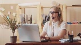En flicka i en vit blus, exponeringsglas och hörlurar med mikrofon sitter på en tabell med en bärbar dator och skriver och talar  arkivfilmer