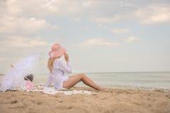 En flicka i en vit skjorta och en rosa hatt som placeras på kusten Royaltyfri Foto