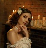 En flicka i en vit tappningklänning med öppna skuldror står mot bakgrunden av ett gammalt piano och stearinljus gotiskt royaltyfria bilder