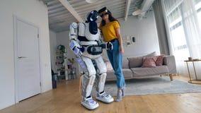 En flicka i VR-exponeringsglas kramar en vit cyborg stock video