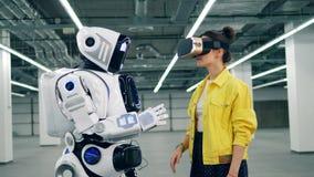 En flicka i VR-exponeringsglas trycker på en hand av en cyborg stock video