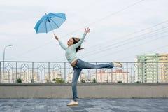 En flicka kör bak ett paraply mot bakgrunden av staden Royaltyfri Foto