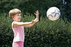 En flicka kastar en boll i parkera Fotografering för Bildbyråer
