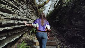 En flicka klättrar stentrappan i bergklyftan och undersöker vaggar bildande arkivfilmer