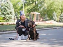 En flicka kramar hennes hund, medan squatting en hund royaltyfri fotografi
