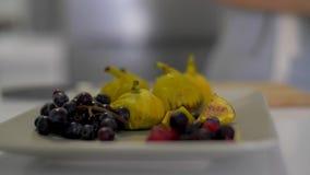 En flicka lägger frukt på en maträtt stock video