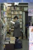 En flicka läser en bok i en bokhandel Asakusa, Tokyo, Japan Arkivbild