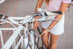 En flicka låser hennes cykel i sommar i stad, ett trottoarkantstaket, ett lås på ramen av cykeln, lösenordval med en nolla arkivbild