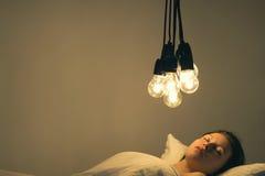 En flicka ligger i säng under stora ljusa kulor på burk ` t för att falla sovande Begreppsbild insomnia psykologi Arkivfoton