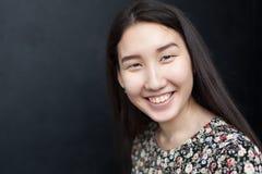 En flicka med asiatiska leenden för ett utseende Arkivfoton