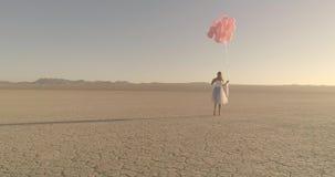 En flicka med ballonger som går i hägringen för ökensjöEl Flyg- surr Oktober 2017 arkivfilmer