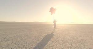 En flicka med ballonger som går i hägringen för ökensjöEl Flyg- surr Oktober 2017 lager videofilmer