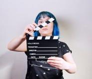 En flicka med blått hår som rymmer en clapper royaltyfria bilder