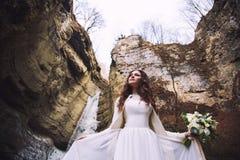 En flicka med blommor från rosor i en chic bröllopsklänning står på en bakgrund av en glaciär i en bergskedja arkivbild