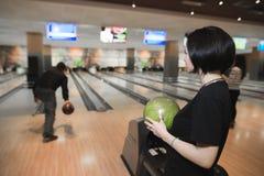 En flicka med en boll för att bowla i hennes handblickar på en annan lek för person` s närmande sig stift för bollbowlinglek Royaltyfria Foton