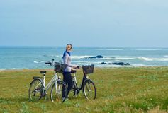 En flicka med cyklar ser havet royaltyfri foto