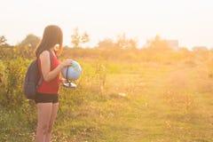 En flicka med det hållande jordklotet för backback Arkivfoto