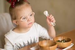 En flicka med Down Syndrome utbildas på Montessori arkivfoto