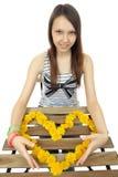 En flicka med en enorm hjärta som komponeras av den gula maskrosen, blommar. Arkivfoto