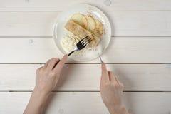 En flicka med en kniv och en gaffel, snitt per stycke av äpplestrudel med glass på den vita trätabellen royaltyfri bild