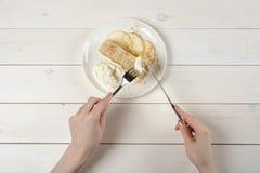 En flicka med en kniv och en gaffel, snitt per stycke av äpplestrudel med glass på den vita trätabellen arkivfoton