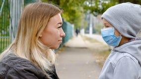 En flicka med ett barn står på vägen i en skyddande medicinsk maskering Tät smog på gatorna Epidemi av influensan stock video