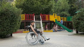 En flicka med ett benbrott sitter i en rullstol framme av lekplatsen arkivfilmer