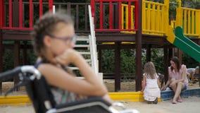 En flicka med ett benbrott sitter i en rullstol framme av lekplatsen stock video