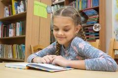 En flicka med ett leende läser en bok i det läs- rummet royaltyfri fotografi
