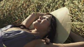En flicka med ett sugrör i hennes mun ligger i fältet och tycker om en varm sommardag härligt barn för hattsugrörkvinna stock video