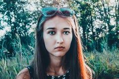 En flicka med en förvirrad framsida ser rak in i kameran arkivfoton