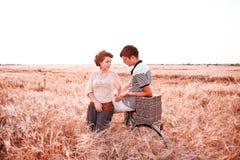 En flicka med en grabb som promenerar ett rågfält med en cykel och ser de royaltyfria foton