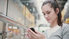 En flicka med härliga örhängen och en hästsvans sitter i ett offentligt ställe som skriver på hennes telefon arkivfilmer
