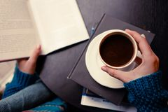 En flicka med kaffe och en bok arkivfoto