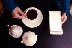 En flicka med kaffe och smartphonen royaltyfria bilder