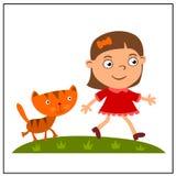 En flicka med en kattunge går på en grön äng arkivbild