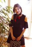 En flicka med kort hår i en svart klänning royaltyfri foto