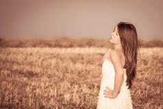 En flicka med långt hår i en vit klänning Royaltyfri Bild