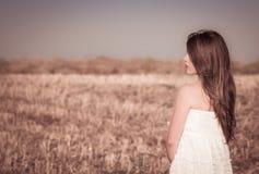 En flicka med långt hår i en vit klänning Arkivfoto