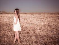En flicka med långt hår i en vit klänning Royaltyfria Foton