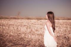 En flicka med långt hår i en vit klänning Royaltyfria Bilder
