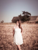 En flicka med långt hår i en vit klänning som poserar i ett sommarfält Arkivfoto