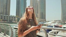 En flicka med långt hår ringer ett meddelande på smartphonen på kajen av den Dubai marina stock video
