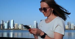 En flicka med l?ngt h?r ringer ett meddelande p? smartphonen p? kajen av Dubai arkivfilmer