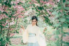 En flicka med långt svart hår som dekoreras med Kandzashi, blommor och långt ben med crystal pärlor Geisha i en bambu arkivfoto