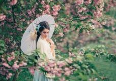 En flicka med långt svart hår som dekoreras med Kandzashi, blommor och långt ben med crystal pärlor Geisha i en bambu royaltyfria foton