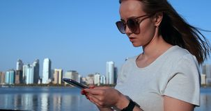 En flicka med l?ngt h?r ringer ett meddelande p? smartphonen p? kajen av Dubai lager videofilmer