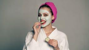En flicka med en maskering på hennes framsida och en handduk på hennes huvud stänger henne ögon med gurkor och skratt Härlig flic lager videofilmer